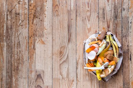 Organic waste in a paper bag on a wooden background with space for text. Top view. Bio garbage ecological concept Stock Photo