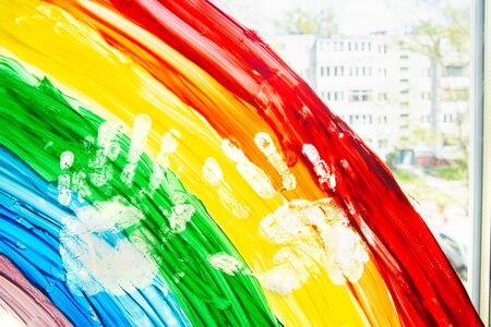 Close up painting rainbow on the window with a handprint. Quarantine with children during coronavirus pandemic. Social media flashmob case the rainbow, lets all be well concept. Banque d'images