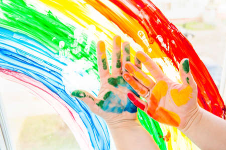 Hands smeared with colorful paint against a rainbow on the window. Stay at home during coronavirus pandemic. Social media campaign for coronavirus prevention, chase the rainbow flashmob.