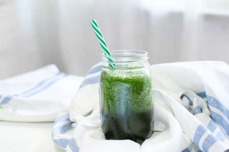 Healthy green smoothie in a mug with a strip of linen cloth on a white table background. Vegan food and healthy summer diet concept Reklamní fotografie