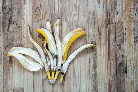 Banana peel on an old wooden background. Organic trash sorting concept