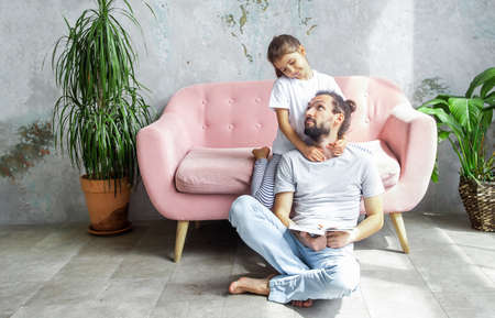 Cute young father is reading a book to his daughter. Happy family togetherness and fatherhood. little girl spend time with their father.
