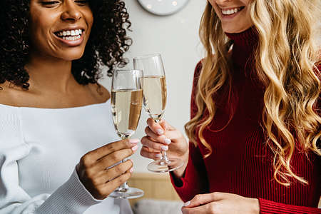 Close up of smiling multiethnic young women friends cheers drink champagne enjoy New year celebration, happy diverse millennial girls in gowns celebrate hen party or New Year night at home