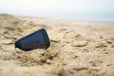 bury: Mobile touch phone in sand on a beach