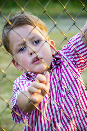 boy behind mesh fence photo