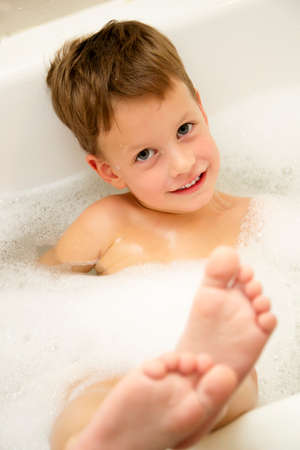 Cute three year old boy taking a bath with foam photo