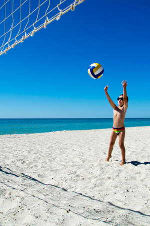 Kid play volleyball on sea beach