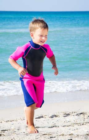 Kind in seinem Taucheranzug verlassen Wasser am Strand
