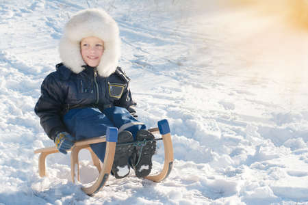 sledging: Cute young boy laughing as he is sledging downhill in snow