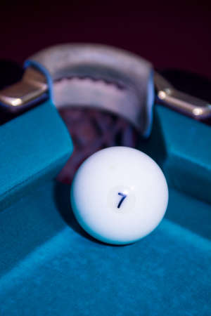 going in: Closeup shot of white ball going in billiard pocket Stock Photo