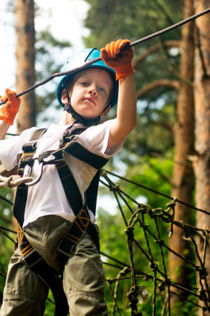 Five year boy on rope-way in forest Stock Photo