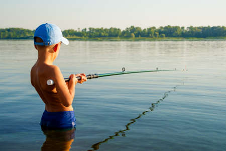 Boy fishing waist deep in water Imagens