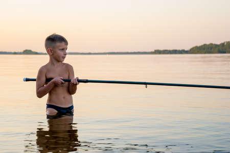 Junge Fischen Taille tief im Wasser