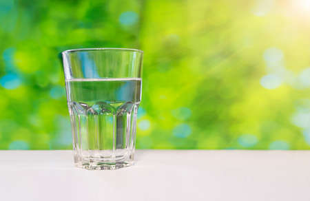 Faceted glass of water on nature background.