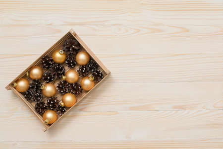 Pine cones with gold balls in the wooden box on a white wooden background. Top view. Flat lay. Space for your text.
