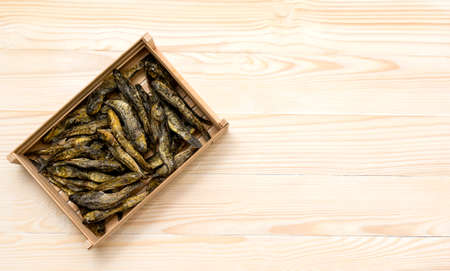 Dried Small fish in wooden box on white wooden background. Beer snack. Space for text.