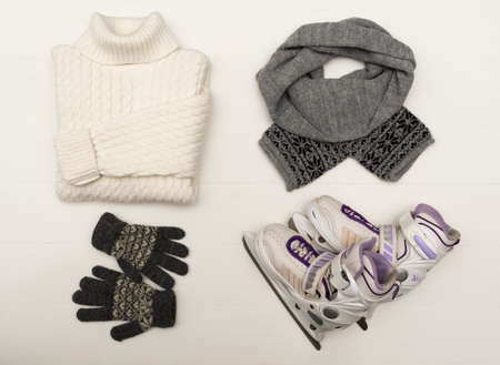 Beauty clothes arrangement with hat, mittens, sweater, scarf and skates flat lay, top view Standard-Bild
