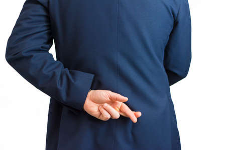 Closeup of a business man with his hand behind his back and fingers crossed. Фото со стока