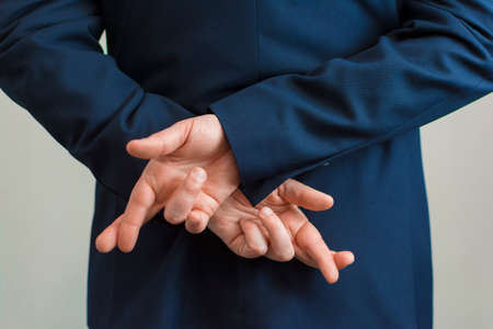 Closeup of a business man with his hands behind his back and fingers crossed Stock Photo