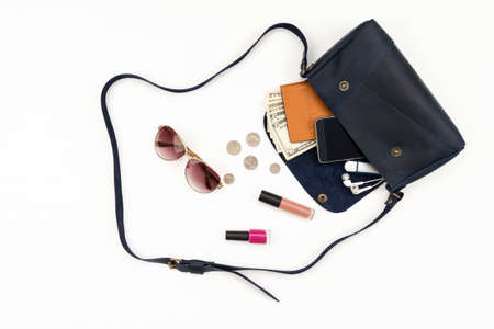 Contents of woman handbag open out with accessories smartphone, passport, earphone, flash-drive and glasses on white