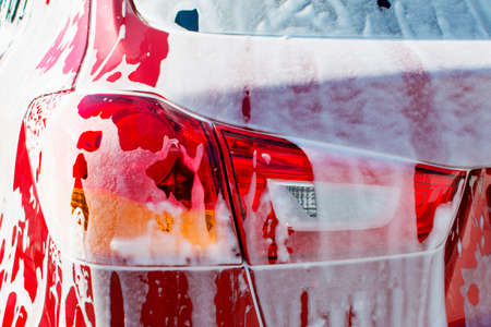 Back view of red compact SUV car with sport and modern design washing with soap. Car covered with white foam Stock Photo