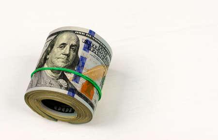 Dolarowa rolka spięta opaską. Walcowane pieniądze na białym tle. Zdjęcie Seryjne