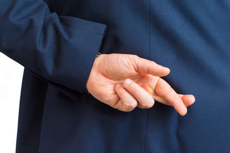 Closeup of a business man with his hands behind his back and fingers crossed.