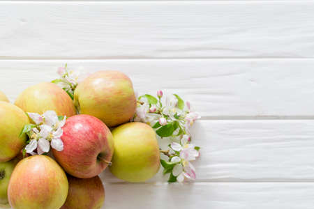 apple flowers and ripe apples on a white wooden background, top view