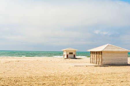 Empty beach. Off season in Black Sea. White beach huts next to the sea.