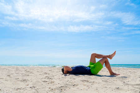 Young man enjoying a vacation, laying up with his legs on the sea shore,
