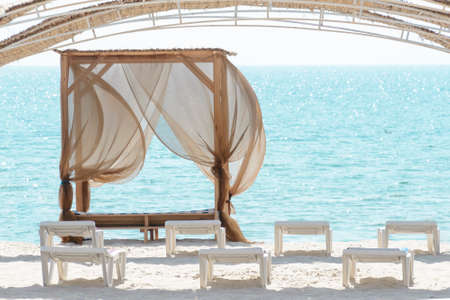 Empty beach beds. Lounge chaise on a sand shore,sun umbrellas omission, empty beach, summer