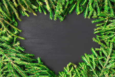 Christmas frame heart shaped made of natural fir branches on black wooden background. Flat lay, top view 写真素材