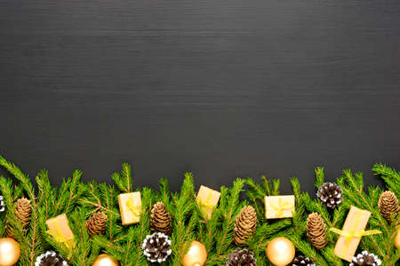 Green fir branches with cones and decorates on black wooden desk. Christmas and New Year border frame. Space for text