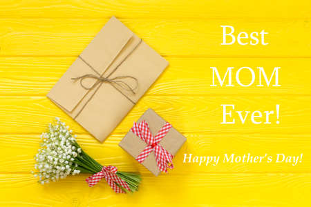 Happy Mothers day text on yellow rustic wooden background. greeting card and gift box concept spring flowers flat lay Stock Photo