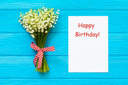 Happy Birthday greeting card and flowers on wooden background Stock Photo