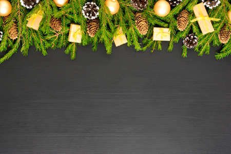 Border made of fir branches with cones and decorates on dark wooden desk. Christmas and New Year background. Space for text
