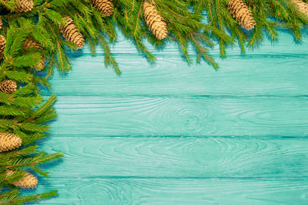 Green fir branches with cones, white decorates on blue wooden texture. Christmas and New Year background. Space for text Stock Photo