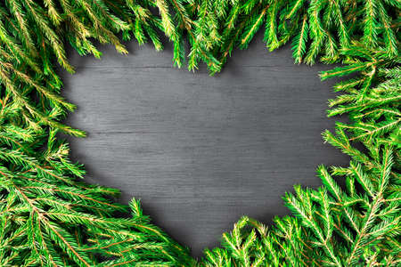 Christmas frame heart shaped made of natural fir branches on dark wooden background. Can be used for BBQ menu