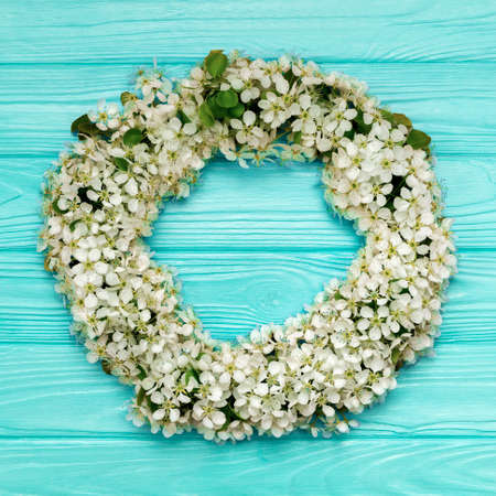 Round frame wreath made of spring flowers and leaves on blue wooden background. Flat lay. Top view