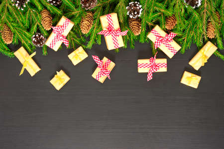 Christmas composition. Border made of gift, fir branches on black background. Flat lay, top view, copy space Stock Photo