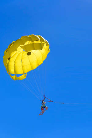 Young active couple enjoying flying with parachute, extreme parasailing activity