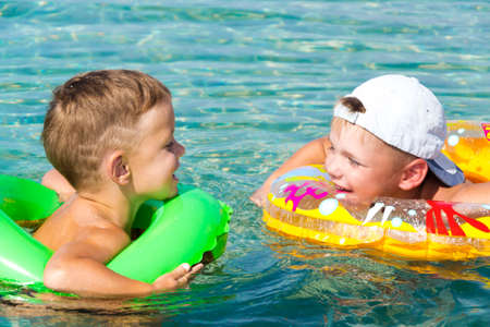 two happy children having fun in the water with inflateble ring Stock Photo