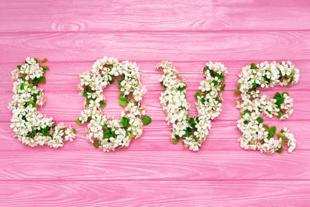Inscription Love made of cherry blossom flowers on pink wooden background. Design elements for Valentines day.