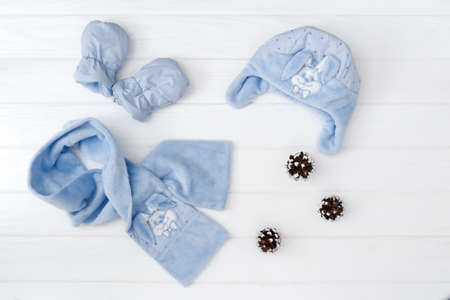 Autumn or winter fashion outfit. Baby boy blue set of clothing on the wooden background. Stock Photo