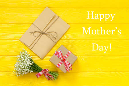 Happy Mothers day text on yellow rustic wooden background. greeting card and gift box concept spring flowers flat lay.