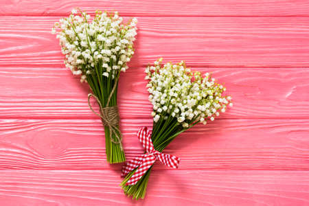 Bouquet of flowers lily of the valley with red ribbon on pinkwooden table from above.