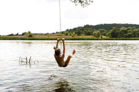 Teenage boy jumping in the river from the swinging rope on sunny summer day Stock Photo - 122263265