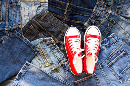 Top view Heap of blue jeans and red sneakers, Jeans background Stock Photo - 122264907