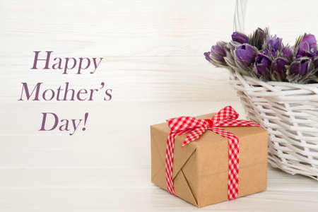 Basket with purple flowers with gift box. Happy Mothers day woodeen background. Greeting card. Stock Photo