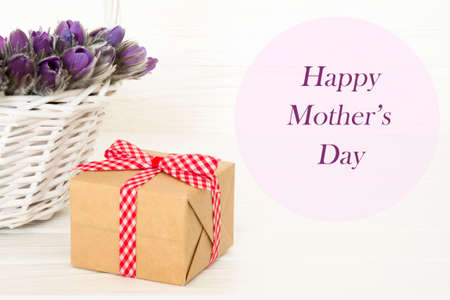 Basket with purple flowers with gift box. Happy Mother's day woodeen background. Greeting card.